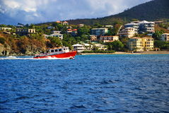 Red Tugboat on Caribbean St. John, USVI. A small red tugboat glides across the blue Caribbean sea off the island of St. John, US Virgin Islands with colorful Royalty Free Stock Photos