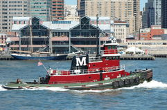 Red tugboat passes South Street Seaport, New York royalty free stock photo