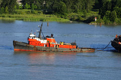 Red tugboat towing a container Stock Photo