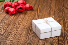 Red tulip bouquet and a gift box on a wooden table. Stock Photos