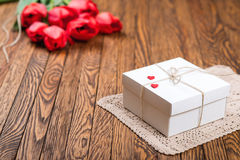 Red tulip bouquet and a gift box on a wooden table. Royalty Free Stock Image