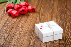 Red tulip bouquet and a gift box on a wooden table. Royalty Free Stock Images
