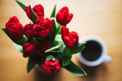 Red Tulip Bouquet Beside White Ceramic Cup Full of Black Liquid stock photo