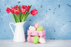 Red tulip flowers and easter eggs. Red tulip flowers bouquet and easter eggs in front of stone wall. Easter greeting card with space for your greetings Stock Images