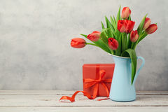 Red tulip flowers bouquet and gift box over rustic background. Women day or birthday celebration Stock Photography