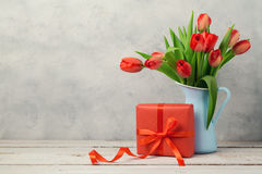 Red tulip flowers bouquet and gift box over rustic background. Women day or birthday celebration Royalty Free Stock Photos