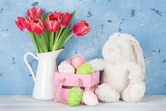Red tulip flowers, eggs and easter rabbit toy Stock Photos