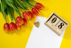 Red tulip flowers near cubic wooden calendar with date of 8 March, wooden heart and sheet of white paper with coopy space. royalty free stock photo