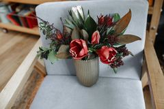 Red Tulip Flowers in Vase on Armchair stock images