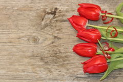 Red Tulip and Wood Grain Background. Five red tulips lying on a weathered wooden plank with red ribbon around the stems. Can be used as a background or border royalty free stock photos