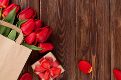 Red tulips bouquet in bag over wood Stock Image