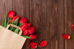 Red tulips bouquet in bag over wood Royalty Free Stock Photos