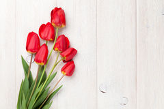 Red tulips bouquet over wood Royalty Free Stock Images