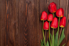 Red tulips bouquet. Over wooden table background with copy space Royalty Free Stock Images
