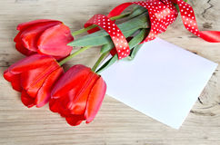 Red tulips bouquet & paper sheet on wooden background. Stock Images