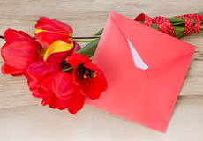 Red tulips bouquet with white paper card & envelope on wooden ta Royalty Free Stock Photos