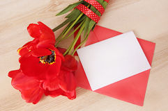 Red tulips bouquet with white paper card&envelope on wooden tabl Stock Photos