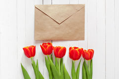 Red tulips and a card in an envelope Royalty Free Stock Photos