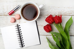 Red tulips, coffee cup and notebook over white wood table. Flat lay Stock Images
