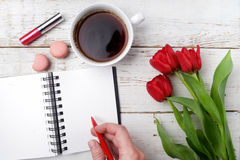 Red tulips, coffee cup and notebook over white wood table. Flat lay Royalty Free Stock Images