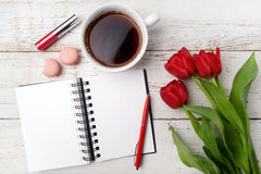 Red tulips, coffee cup and notebook over white wood table. Flat lay Royalty Free Stock Image