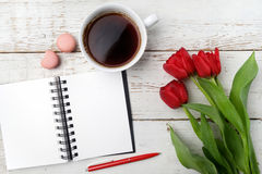 Red tulips, coffee cup and notebook over white wood table. Flat lay Stock Photography