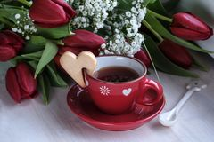 Red tulips and cup of tea. With cookie heart on the table royalty free stock image