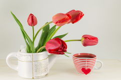 Red tulips with a cup of tea Stock Image