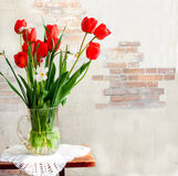 Red tulips and daffodils in a vase Stock Photography