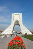 Red Tulips in Front of Azadi Monument in Tehran. TEHRAN - APRIL 1: Azadi Monument behind red tulips against blue sky on April 1, 2014 in Tehran, Iran. Azadi stock photos