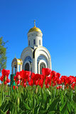 Red tulips in front of a Christian church Royalty Free Stock Photos