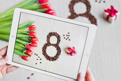 Red tulips, gift box, grain coffee and tablet in hand Stock Images