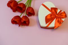 Red tulips and gift box in heart shape with red bow on pink pastel background. Beautiful spring floral layout. Greeting card for. Valentine`s, women`s or mother stock photo