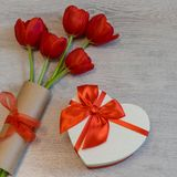 Red tulips and gift box in heart shape with red bow on light wooden background. Beautiful spring floral layout. Greeting card for. Valentine`s, women`s or stock photo
