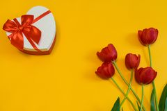 Red tulips and gift box in heart shape with red bow on yellow background. Beautiful spring floral layout. Greeting card for. Valentine`s, women`s or mother`s stock images