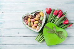 Red tulips and gift box with macaroons Stock Images