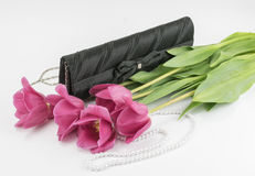 Red tulips, handbag and bead on a white background Stock Photos