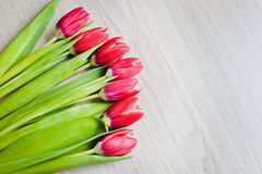 Red tulips are on the table Stock Photos