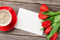 Red tulips, Valentines day greeting card and coffee. Cup over wooden table. Top view with copy space Stock Images