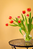 Red tulips in a vase on mosaic table. Stock Photography