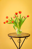 Red tulips in a vase on mosaic table. Royalty Free Stock Photography