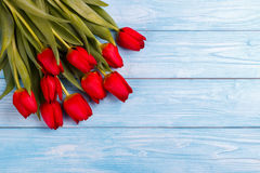 Red tulips on wooden table Royalty Free Stock Image