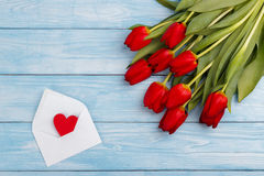 Red tulips on wooden table Stock Image