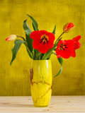 Red tulips in yellow vase Royalty Free Stock Image