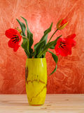Red tulips in yellow vase on wooden table Royalty Free Stock Photos