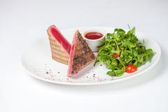 Red tuna steak garnished with arugula. Isolated on white background Royalty Free Stock Photography