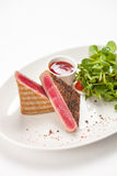 Red tuna steak garnished with arugula Royalty Free Stock Photos