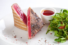 Red tuna steak garnished with arugula. On white background Royalty Free Stock Images