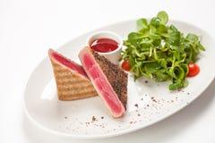 Red tuna steak garnished with arugula. On white background Stock Photo