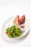 Red tuna steak garnished with arugula. On white background Stock Image
